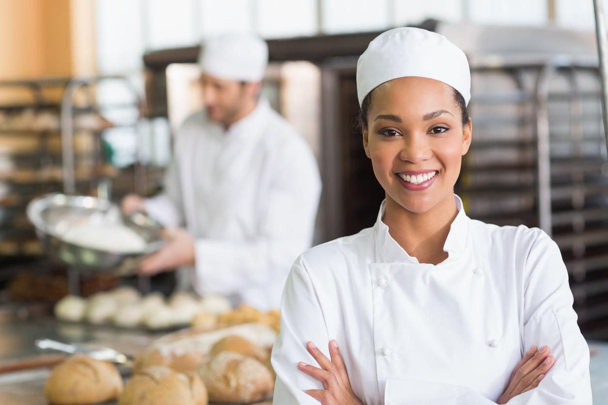 Une femme dans les cuisines d'une boulangerie avec un homme derrière