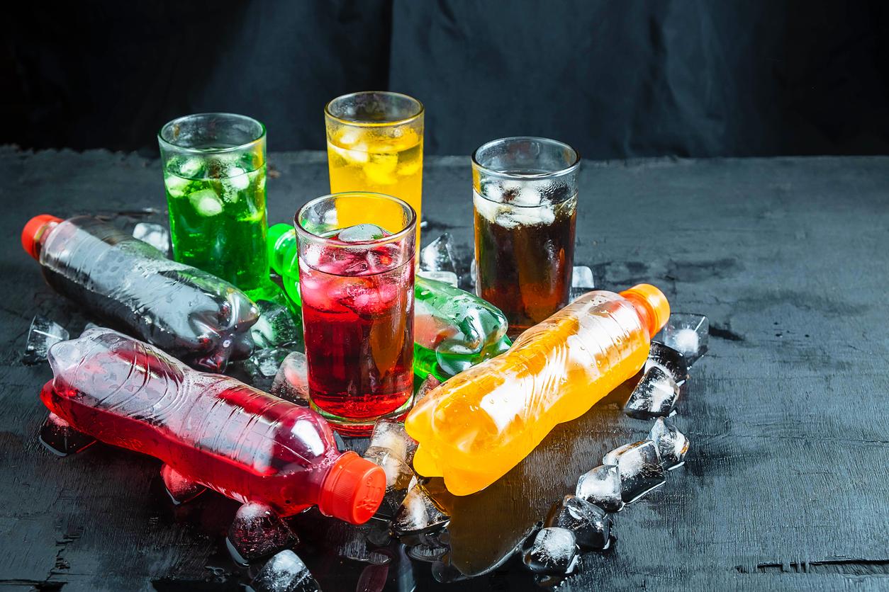 Des bouteilles de soda en plastique avec des verres remplis