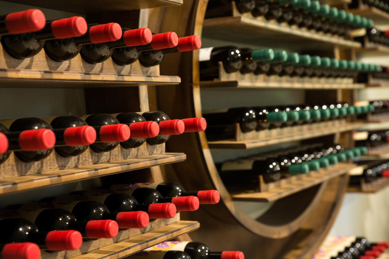 Des bouteilles de vins rangés contre un mur dans une cave à vin
